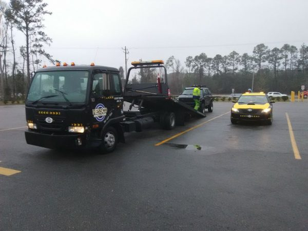 black tow truck about to tow a jeep in jacksonville fl